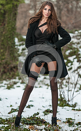 Portrait of young beautiful woman outdoor in winter scenery. Sensual brunette with long legs in black stockings posing fashionable
