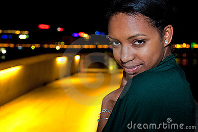 Portrait of young black woman in city at night.
