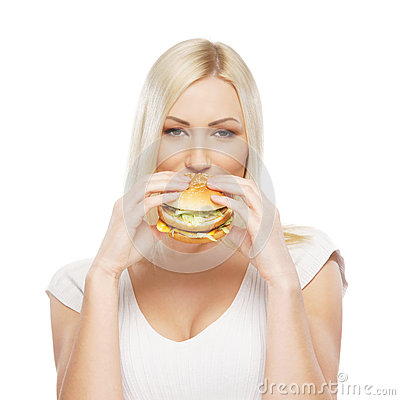 Portrait of a young blond woman eating a burger