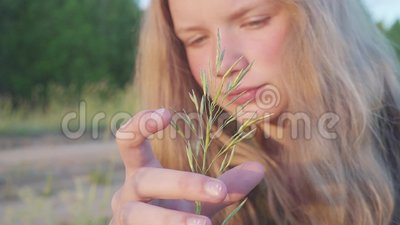 Portrait of the young blonde girl 11 years old. Pensively and dreamily looks at the blade of grass. Hd stock video footage