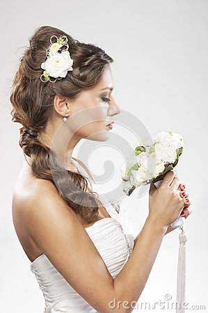 Portrait of a young bride holding white roses