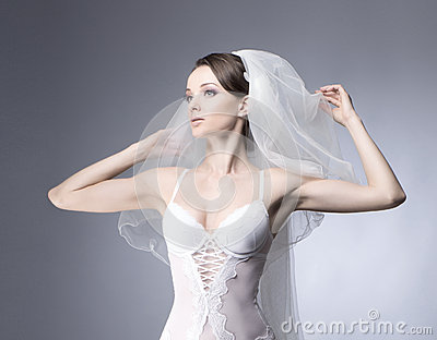 Portrait of a young bride posing in white lingere
