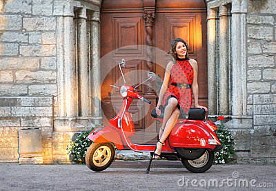 Portrait of a young brunette on an old red scooter
