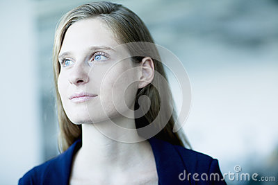 Portrait of young businesswoman looking away in contemplation