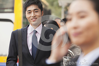 Portrait of young, confident businessman using his mobile phone outdoors in the street, Beijing, China