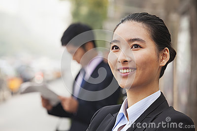 Portrait of young, confident businesswoman looking away and smiling in the street, Beijing, China