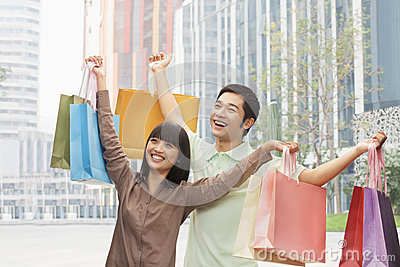 Portrait of young couple posing with shopping bags in hands, Beijing, China