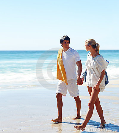 Portrait of a young couple roaming on the beach