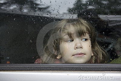 Portrait young girl looking through window