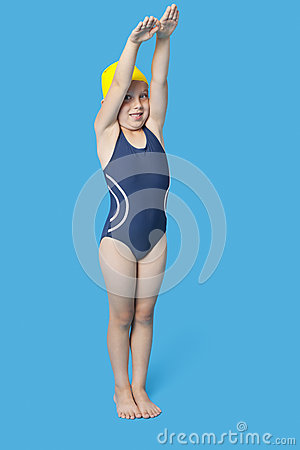 Portrait of a young girl in swimwear with hands raised over blue background