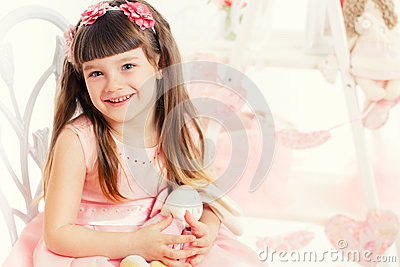 Portrait of young girl with a toy in the hands of