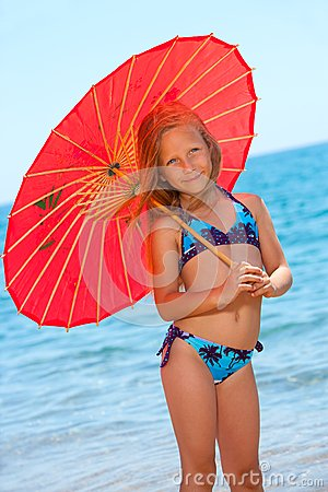 Portrait of young girl with umbrella on beach.