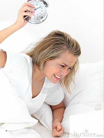 Portrait of young irritated woman banging alarm c
