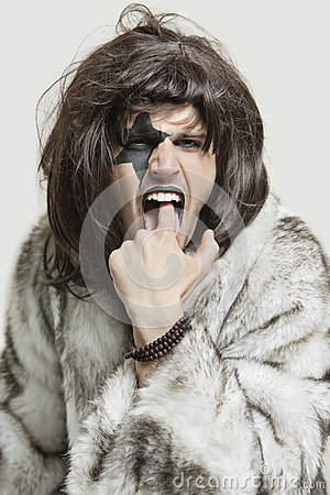 Portrait of young man in fur coat with finger in mouth against gray background