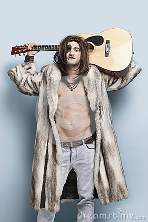 Portrait of young man in fur coat holding guitar against light blue background