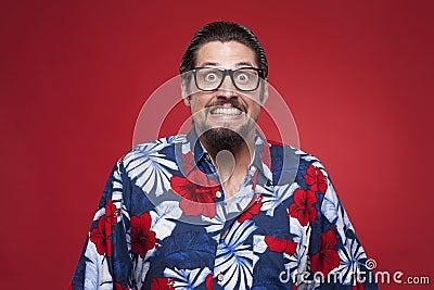 Portrait of a young man in Hawaiian shirt clenching teeth