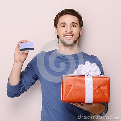 Portrait of young man holding gift box and a credit card. Handso
