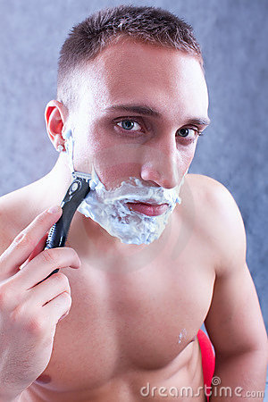 Portrait of a young man shaving his beard