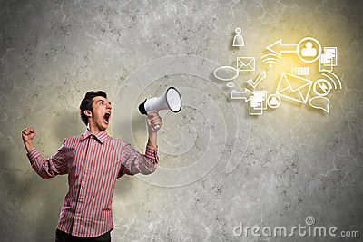 Portrait of a young man shouting using megaphone