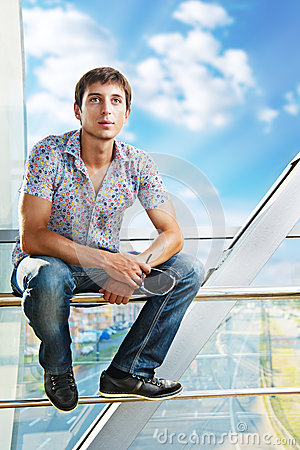 Portrait of a young man sitting on the railing