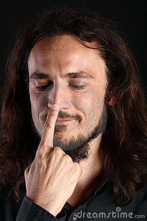 Portrait of young man touching nose with finger