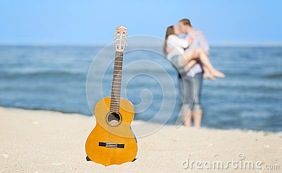 Portrait of young man and woman on a beach and guitar
