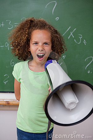 Portrait of a young schoolgirl screaming through a megaphone