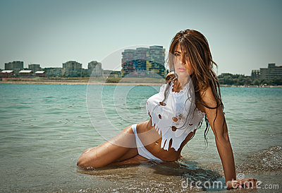 Portrait of young sexy brunette girl in white bikini and wet t-shirt at the beach