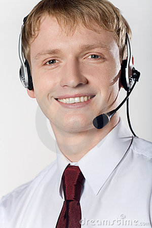 Portrait of young smiling business man with headset on white