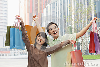 Portrait of young, smiling couple going shopping and holding colorful shopping bags on the street, outdoors in Beijing, China
