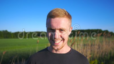 Portrait of young smiling man standing at rural environment. Handsome guy with beard looking into camera with beautiful. Landscape at background. Close up of stock video footage