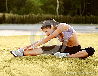 Portrait of Young Sporty Woman Doing Stretching Exercise. Athlet