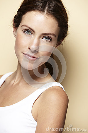 Portrait of young woman, against beige background Stock Photo