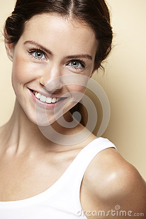Portrait of a young woman, against beige background Stock Photo