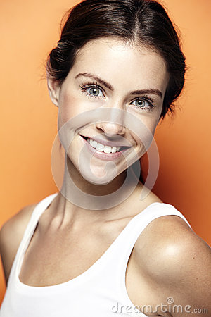 Portrait of a young woman, against orange background Stock Photo