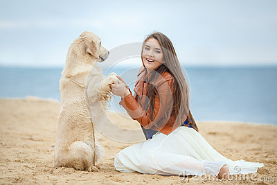 Portrait of a young woman with a dog on the beach