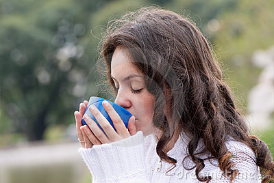 Portrait of the young woman drinking hot tea