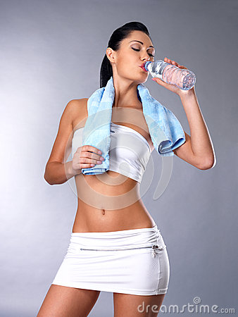 Portrait of young woman drinking water with towel