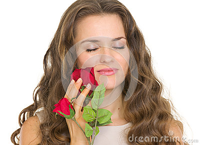 Portrait of young woman enjoying red rose