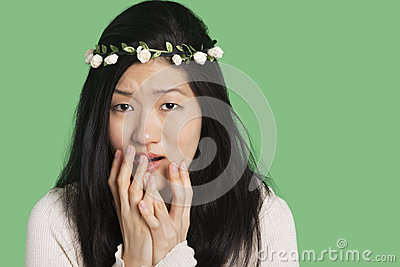 Portrait of a young woman expressing fear and anxiety over green background