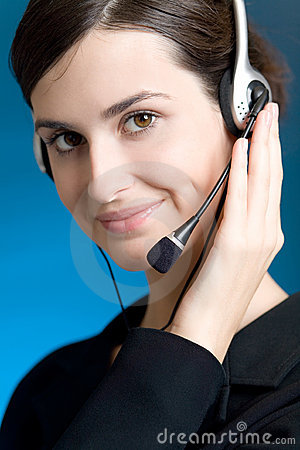 Portrait of young woman with headset, on blue background, smiling