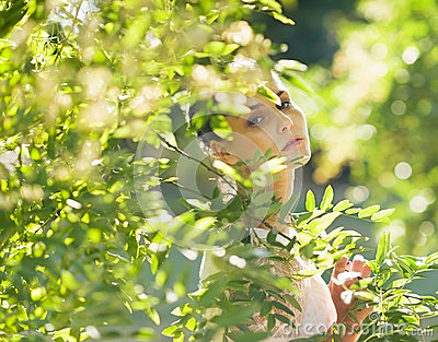 Portrait of young woman hiding in foliage