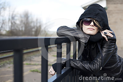 Portrait of Young Woman Leaning on  Metal Fencing