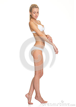 Portrait of young woman in lingerie checking body Stock Photo