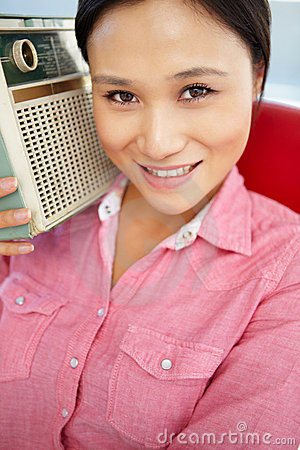 Portrait of young woman listening to radio