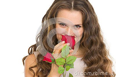 Portrait of young woman smelling red rose
