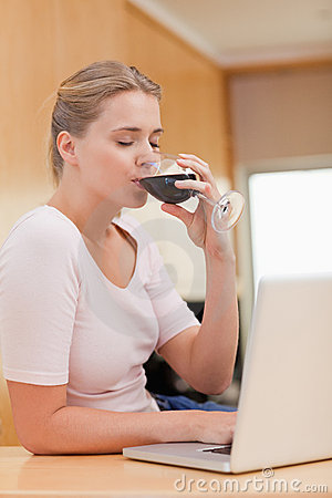 Portrait of a young woman using a laptop while drinking red wine