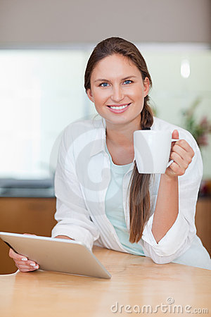 Portrait of a young woman using a tablet computer while drinking
