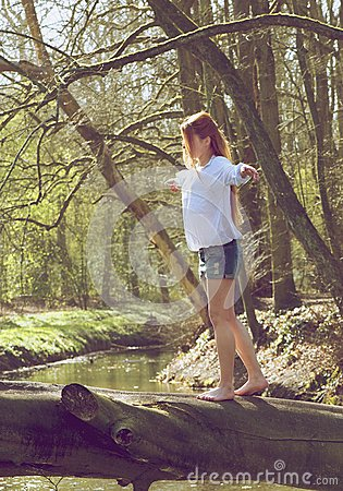 Portrait of a young woman walking over tree trunk