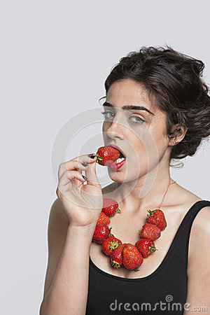Portrait of a young woman wearing strawberry necklace as she eats one piece over gray background